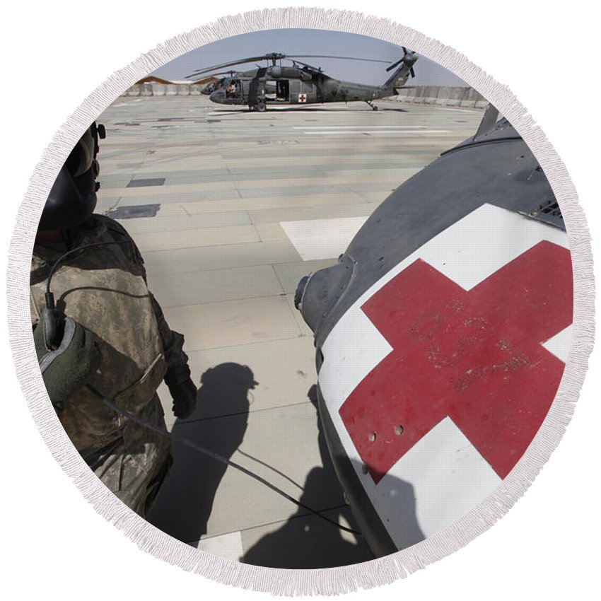 Uh-60 Blackhawk Round Beach Towel featuring the photograph U.s. Army Crew Chief Inspects by Stocktrek Images
