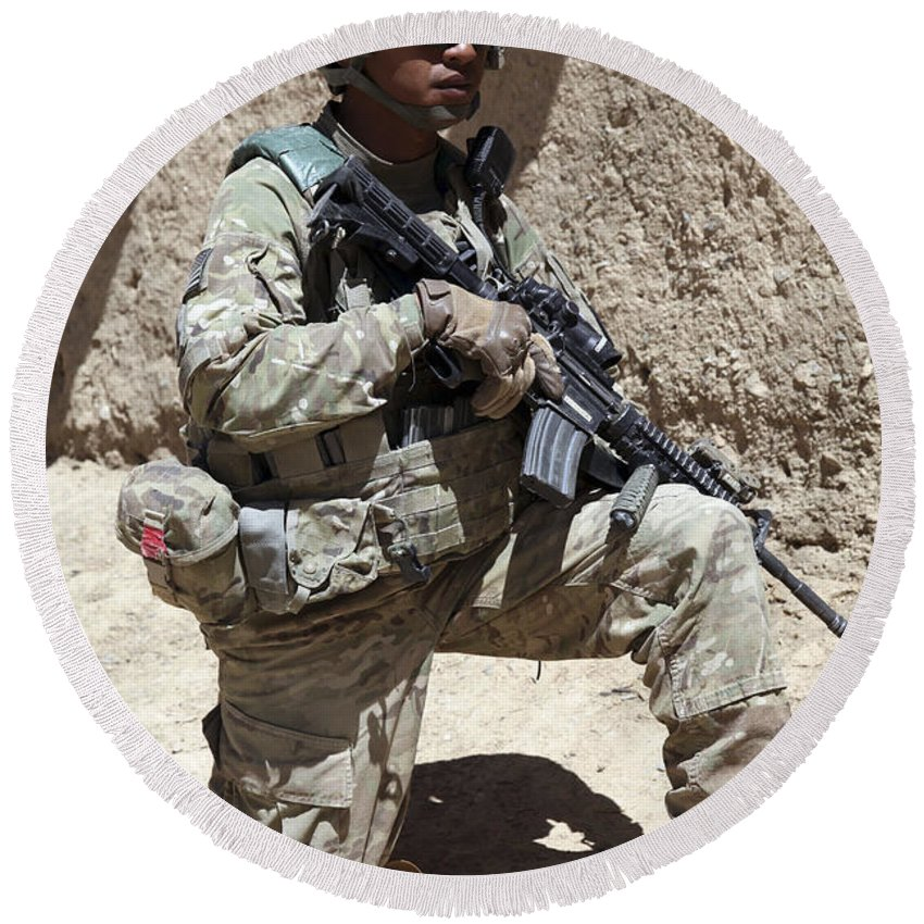 Afghanistan Round Beach Towel featuring the photograph U.s. Army Soldier Takes A Knee While by Stocktrek Images