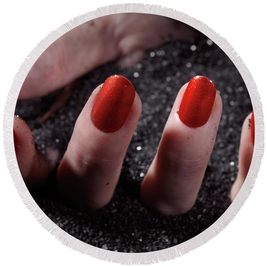 Manicure Round Beach Towel featuring the photograph Woman Hand With Red Nail Polish Buried In Black Sand by Oleksiy Maksymenko