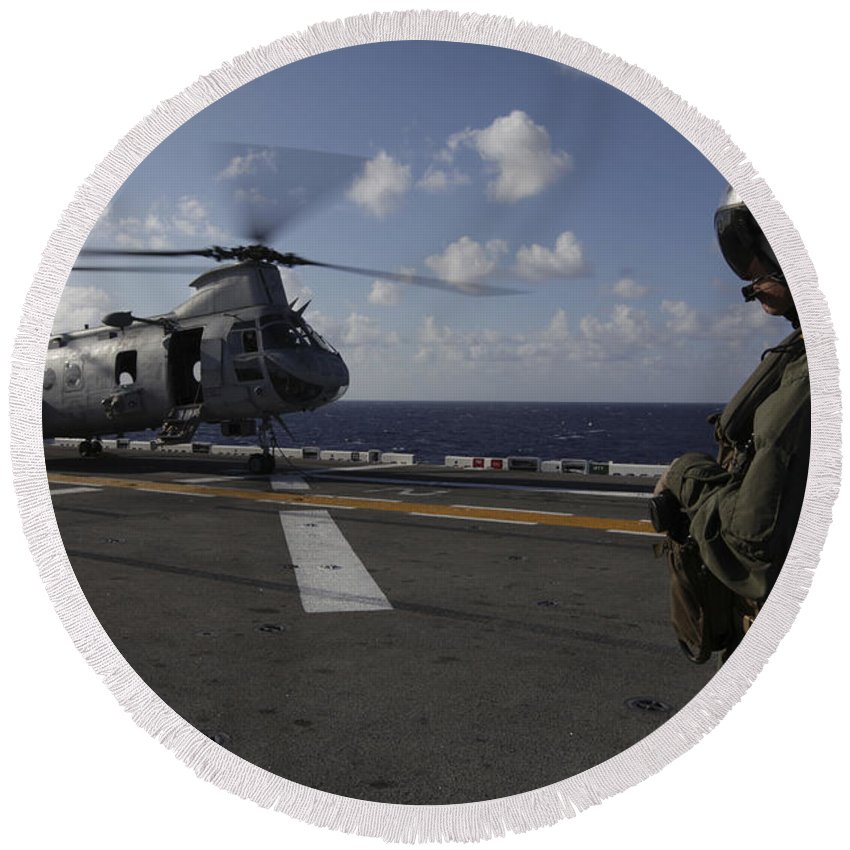 Military Round Beach Towel featuring the photograph A Crew Chief Watches A Ch-46e Sea by Stocktrek Images