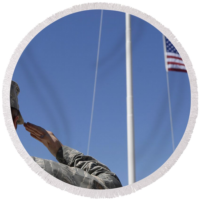 Soldier Round Beach Towel featuring the photograph A Soldier Salutes The American Flag by Stocktrek Images