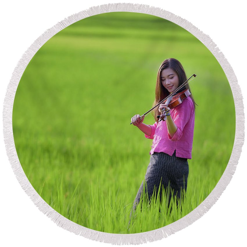 Violin Round Beach Towel featuring the photograph A Young Girl In A Folk Costume Plays A Vivaro In A Green Rice Fi by Somchai Sanvongchaiya