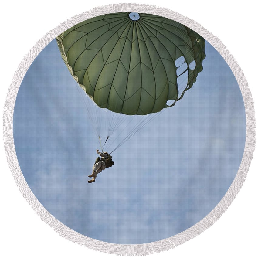 Airman Round Beach Towel featuring the photograph An Airman Descends Through The Sky by Stocktrek Images