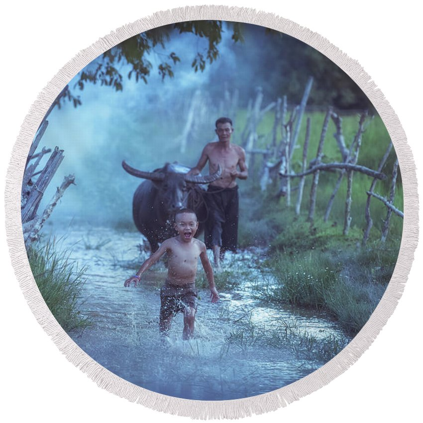 Running Round Beach Towel featuring the photograph Asian Boy Playing Water With Dad And Buffalo by Somchai Sanvongchaiya