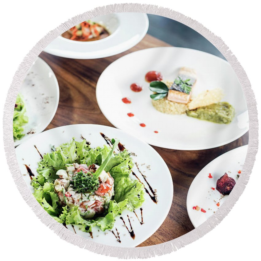 Artistic Round Beach Towel featuring the photograph Mixed Modern Gourmet Fusion Food Dishes On Table by Jacek Malipan