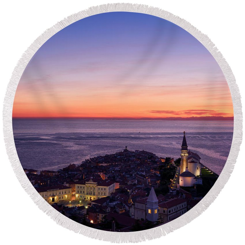 Piran Round Beach Towel featuring the photograph Purple Light On The Adriatic Sea After Sundown With Lights On Pi by Reimar Gaertner
