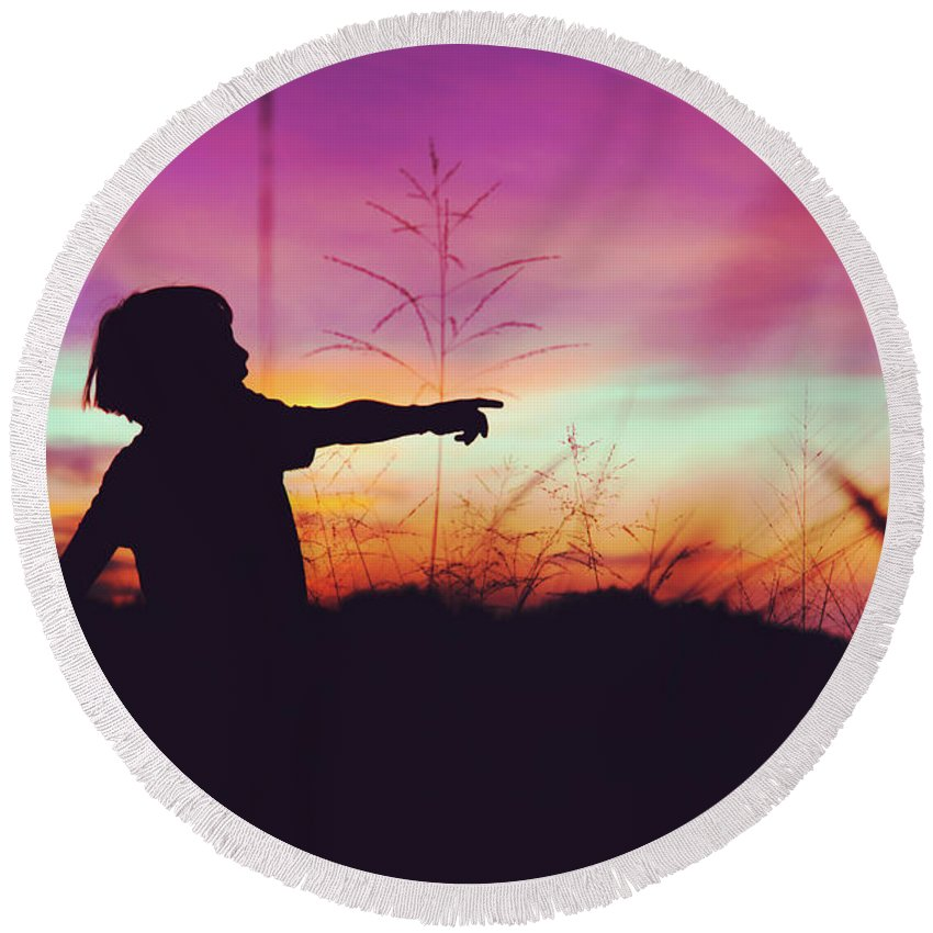Active Round Beach Towel featuring the photograph Silhouette Of A Playful Boy Pointing With Finger In The Field During Beautiful Sunset by Srdjan Kirtic