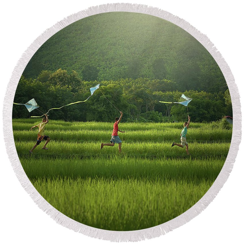 Happy Round Beach Towel featuring the photograph Three Boys Are Happy To Play Kites At Summer Field In Nature In by Somchai Sanvongchaiya