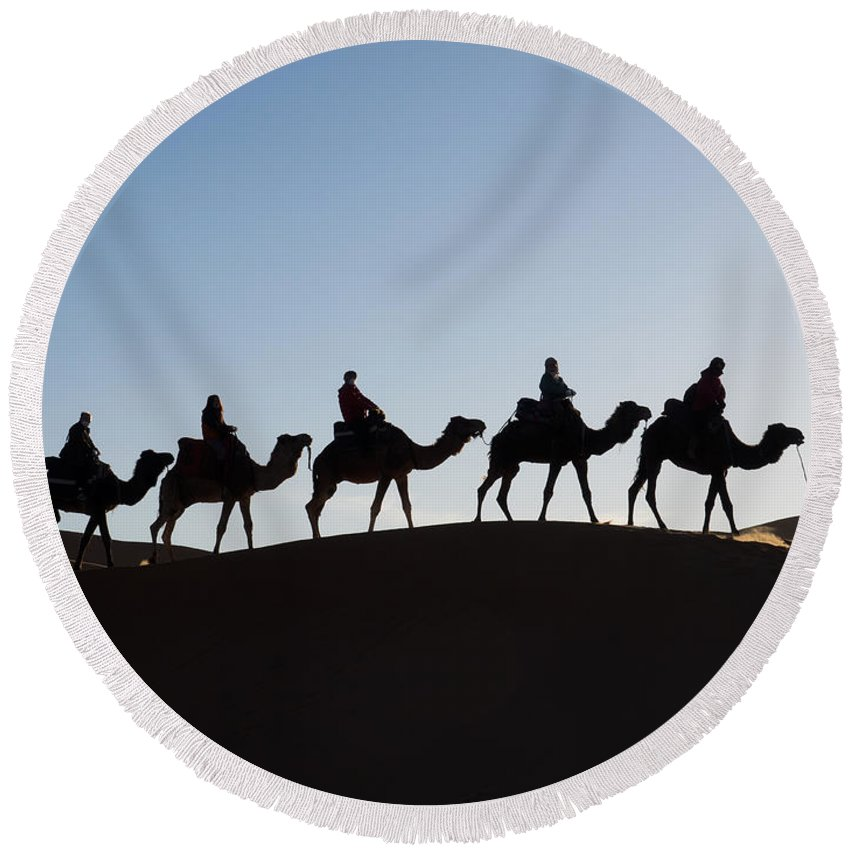 Photography Round Beach Towel featuring the photograph Tourists On Camels Along Top Of Erg by Panoramic Images