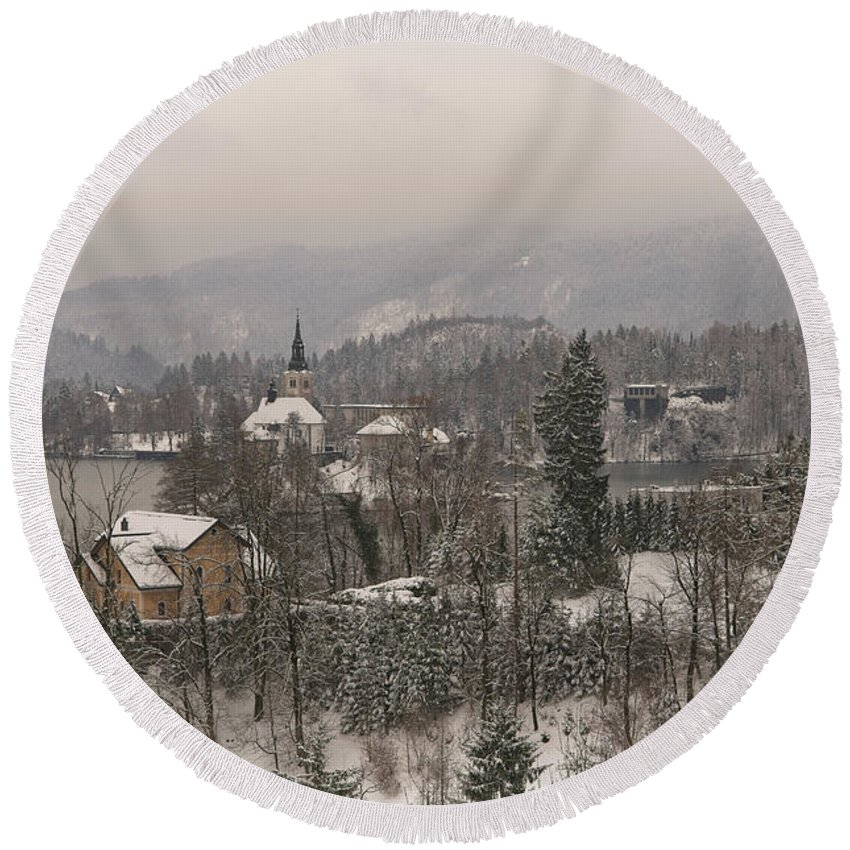 Christmas Round Beach Towel featuring the photograph Snowy Bled In Slovenia by MSVRVisual Rawshutterbug