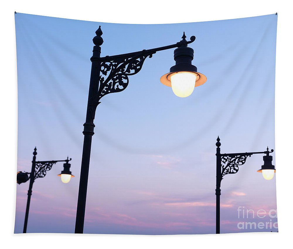 Streetlamps Tapestry featuring the photograph Street Lamps Over Sunset Sky Background by Oleksiy Maksymenko