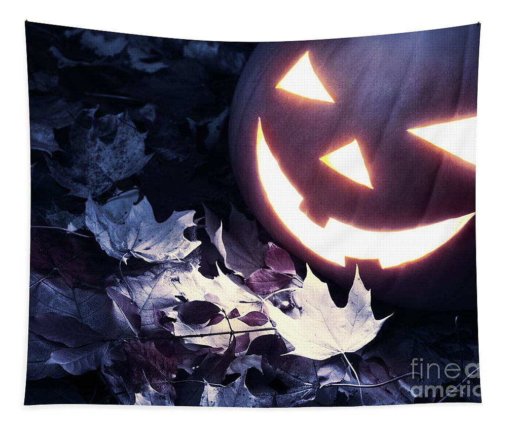 Halloween Tapestry featuring the photograph Spooky Jack-o-lantern On Fallen Leaves by Oleksiy Maksymenko