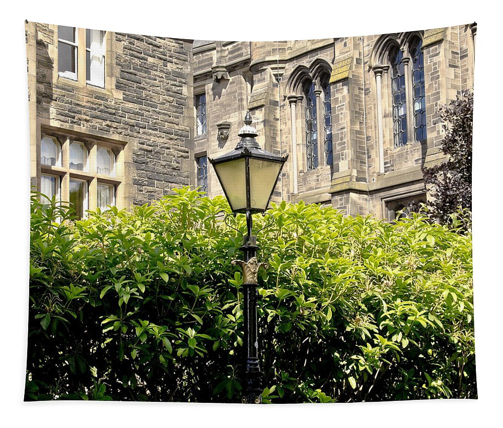 Lamppost Tapestry featuring the photograph Lamppost In Front Of Green Bushes And Old Walls. by Elena Perelman