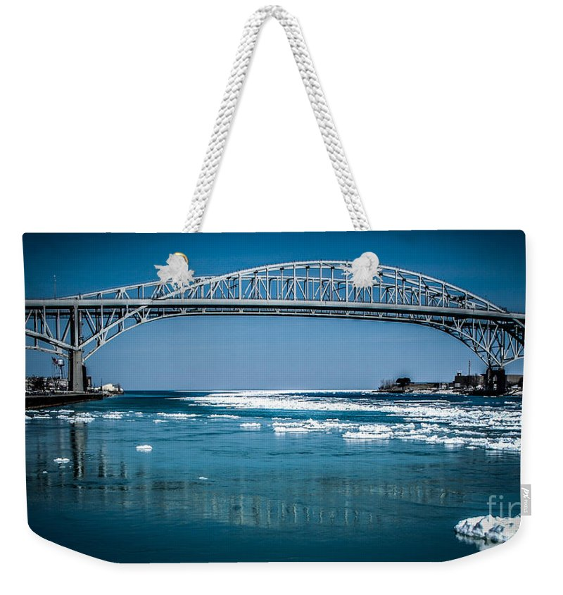 Ice Weekender Tote Bag featuring the photograph Blue Water Bridges With Reflection And Ice Flow by Ronald Grogan