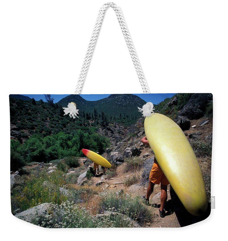 Action Weekender Tote Bag featuring the photograph A Couple Carries Their Kayaks by Corey Rich