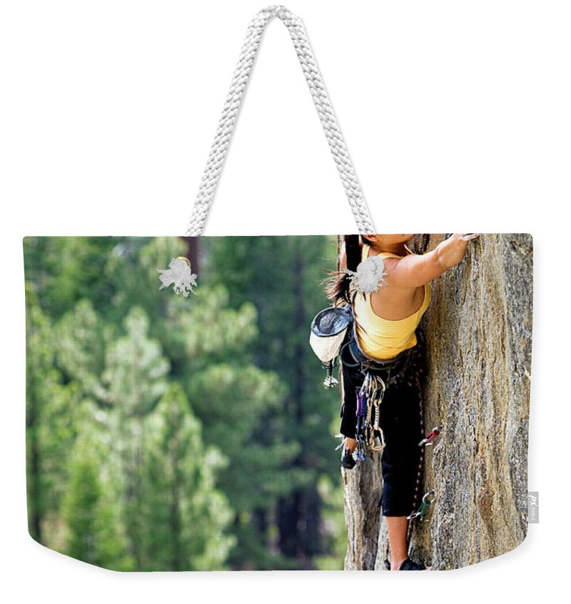 Action Weekender Tote Bag featuring the photograph Attractive Woman Rock Climbing High by Corey Rich