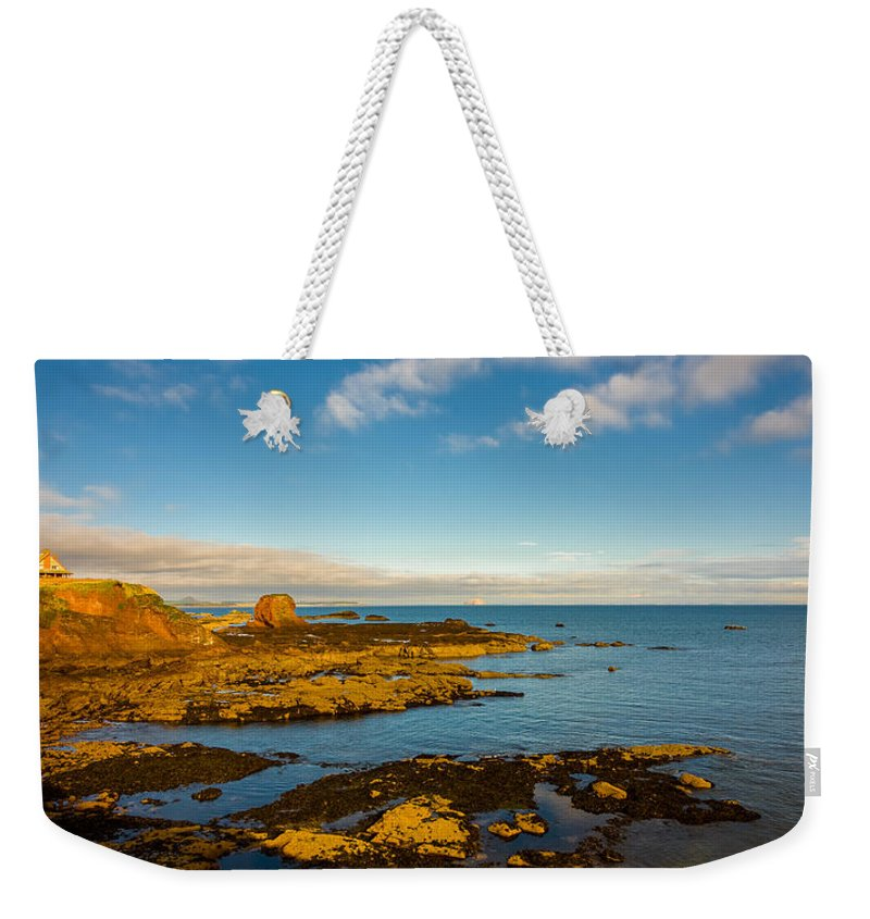 Bass Weekender Tote Bag featuring the photograph Bass Rock From Dunbar by Mark Llewellyn