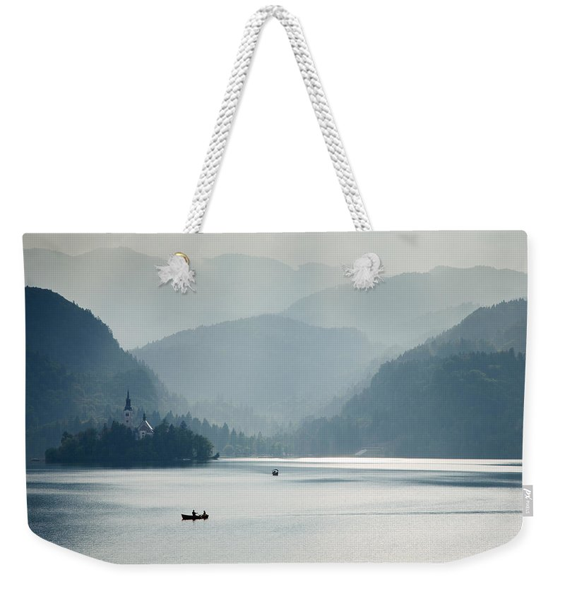 Bled Weekender Tote Bag featuring the photograph Breaking Through The Mist by Ian Middleton