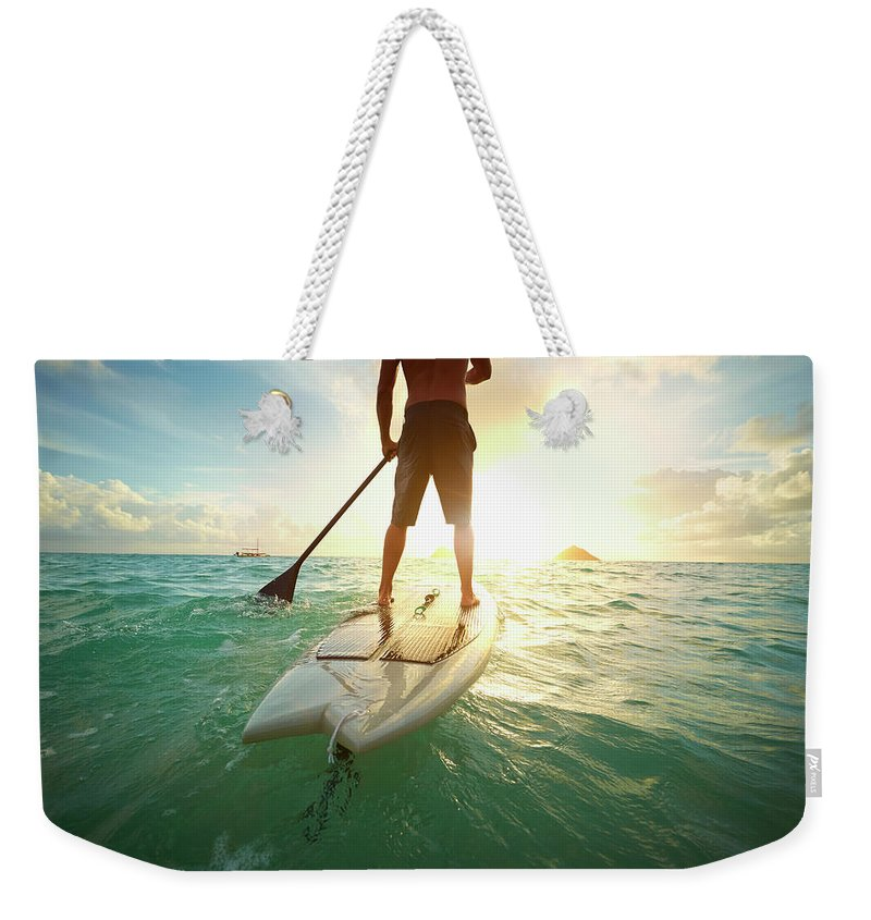 Tranquility Weekender Tote Bag featuring the photograph Caucasian Man On Paddle Board In Ocean by Colin Anderson Productions Pty Ltd