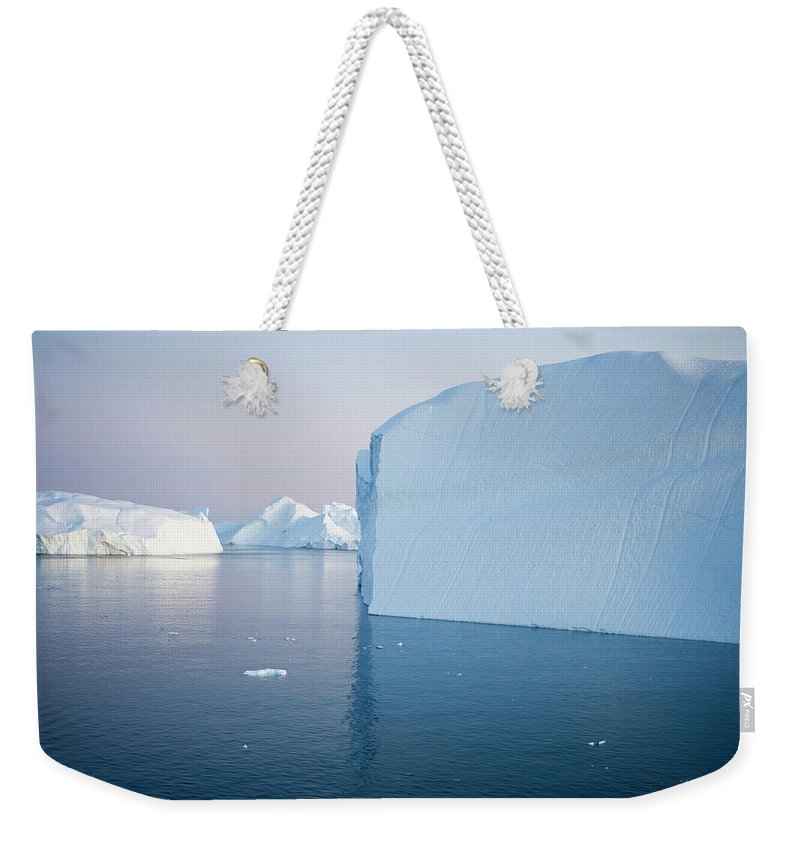 Melting Weekender Tote Bag featuring the photograph Icebergs Of Ilulissat Kangerlua by Holger Leue