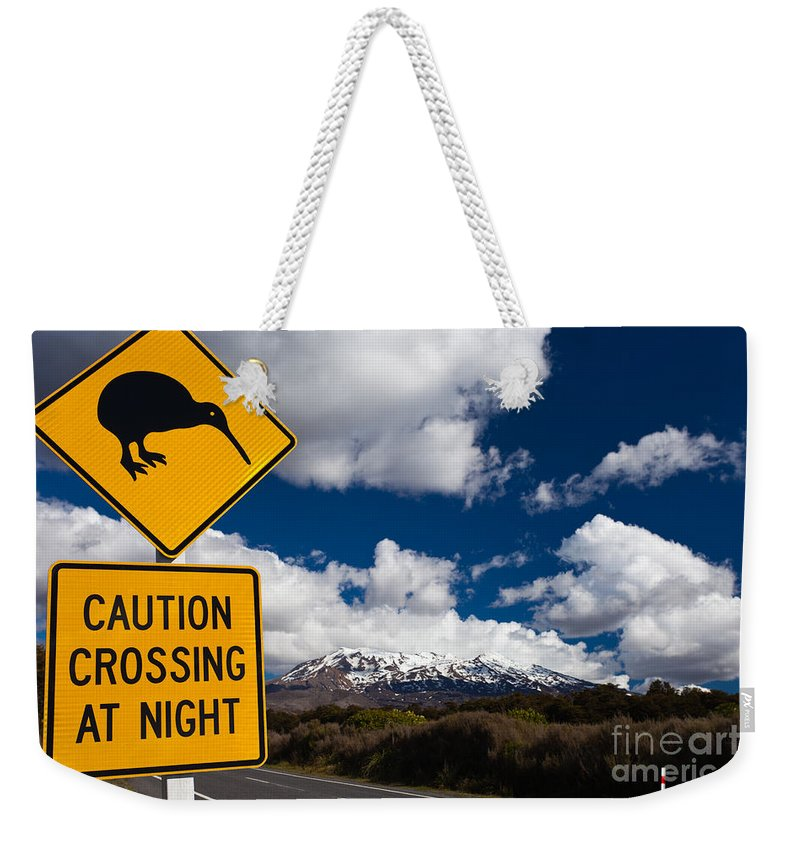 Mount Weekender Tote Bag featuring the photograph Kiwi Crossing Road Sign And Volcano Ruapehu Nz by Stephan Pietzko