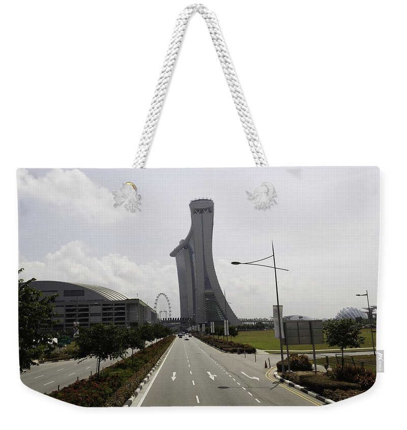 Action Weekender Tote Bag featuring the photograph Marina Bay Sands And Singapore Flyer As Seen From A Distance by Ashish Agarwal