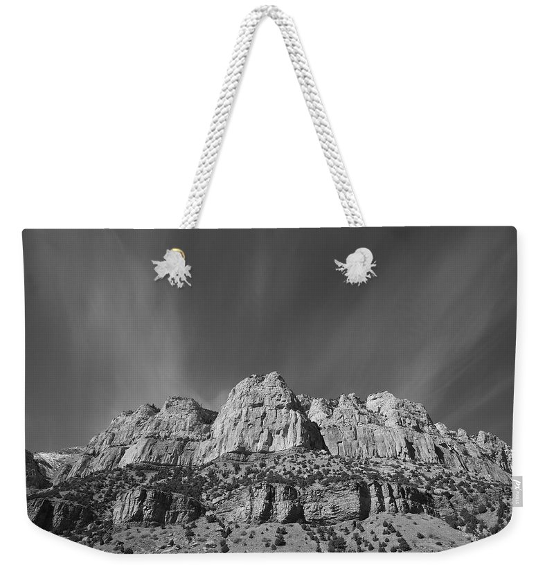 Alpine Weekender Tote Bag featuring the photograph Mountain Peaks And Shimmering Sky by Frank Romeo