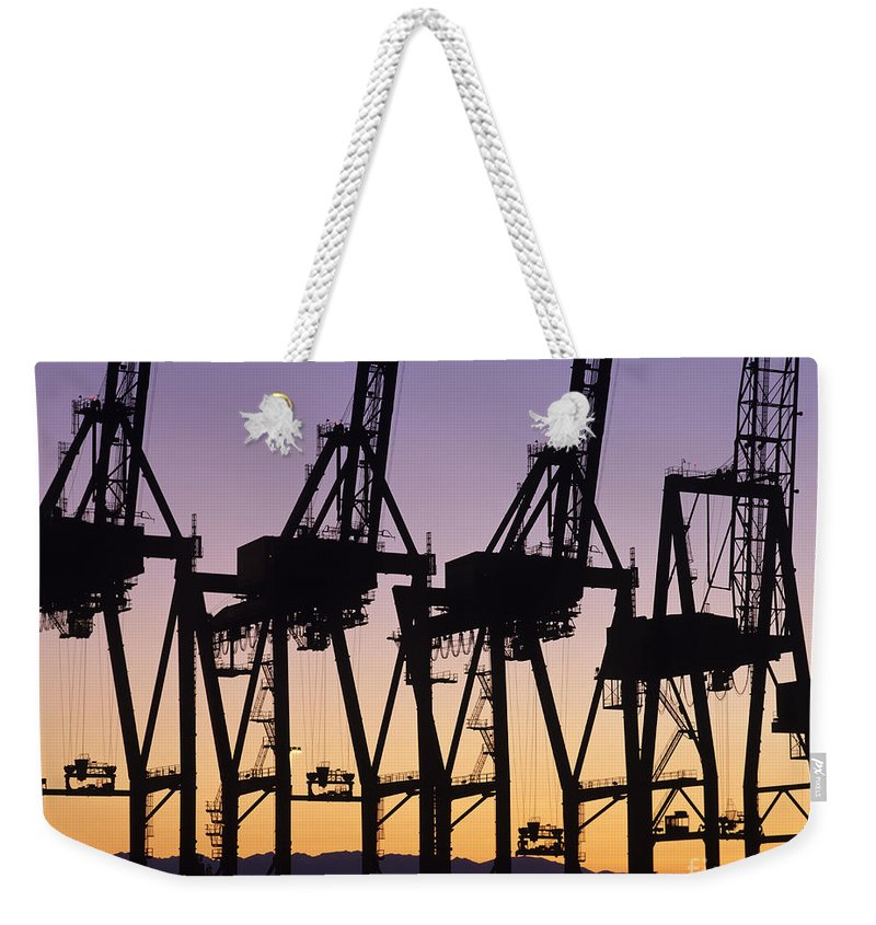 Load Weekender Tote Bag featuring the photograph Port Of Seattle Cranes Silhouetted by Jim Corwin