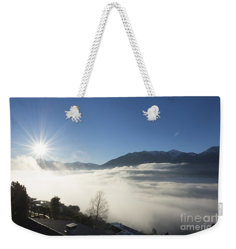 Sea Of Fog Weekender Tote Bag featuring the photograph Sea Of Fog With Sunbeam by Mats Silvan