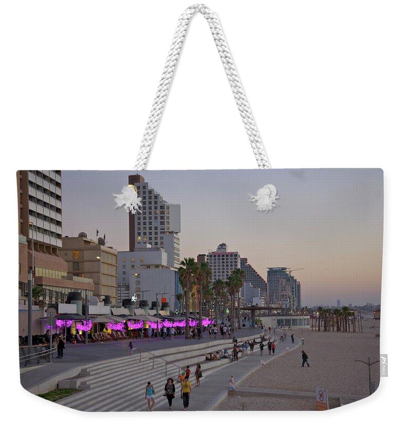 People Weekender Tote Bag featuring the photograph Seaside Promenade Of Tel Aviv At Dusk by Barry Winiker