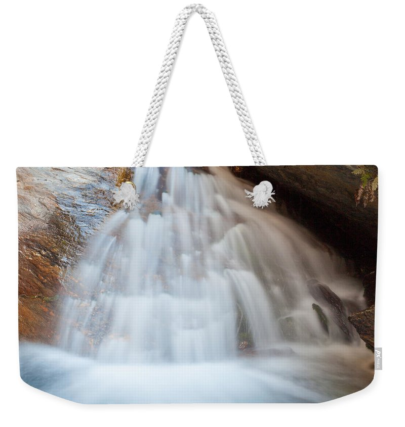 Cascade Weekender Tote Bag featuring the photograph Small Waterfall Casdcading Over Rocks In Blue Pond by Stephan Pietzko