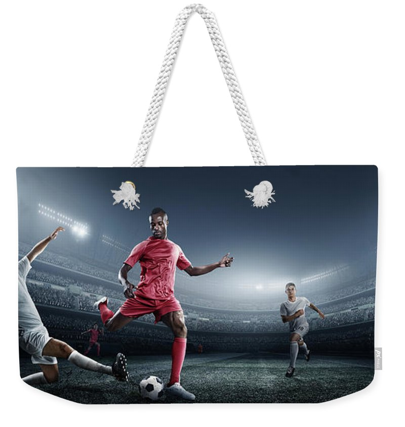 Soccer Uniform Weekender Tote Bag featuring the photograph Soccer Player Kicking Ball In Stadium by Dmytro Aksonov