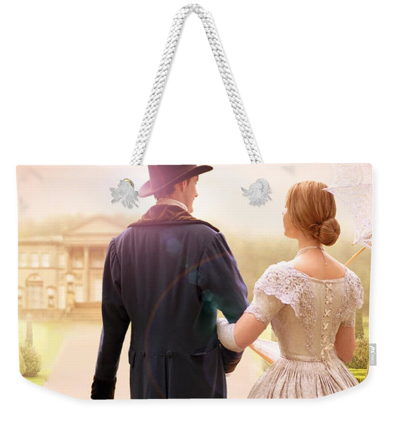 Victorian Weekender Tote Bag featuring the photograph Victorian Couple Walking Towards A Country Estate by Lee Avison