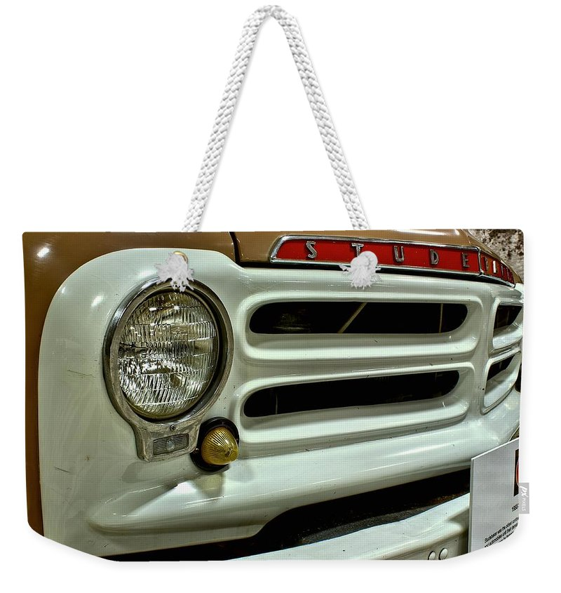 1955 Weekender Tote Bag featuring the photograph 1955 Studebaker Headlight Grill by Michael Gordon