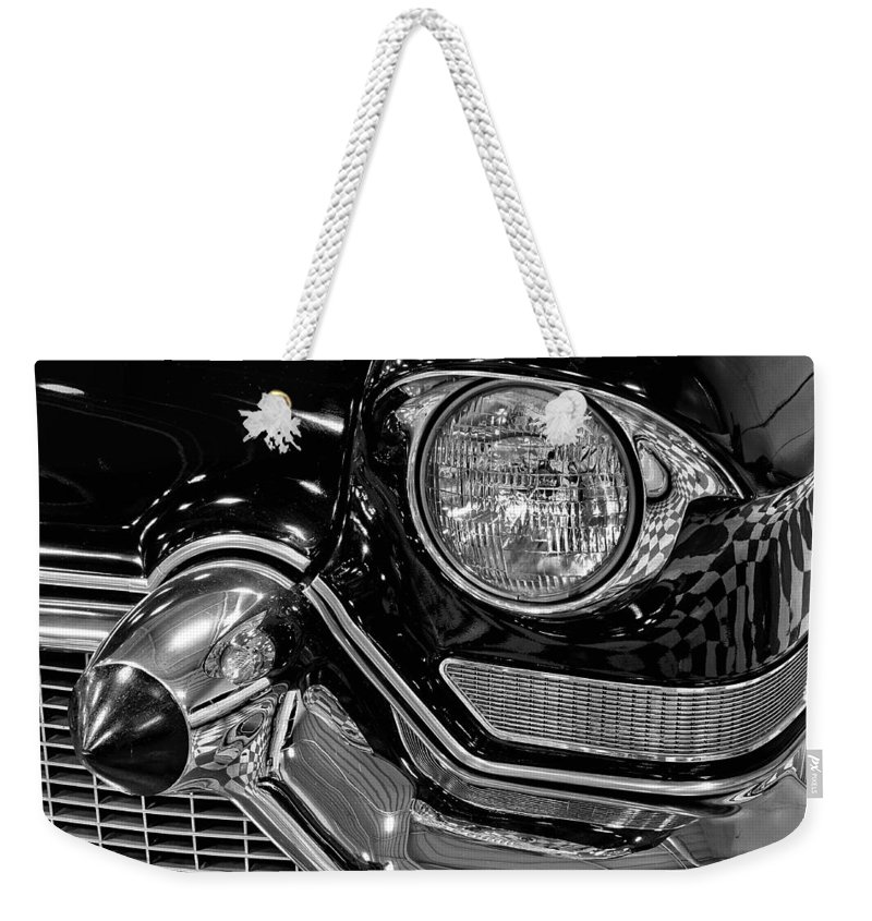 1957 Weekender Tote Bag featuring the photograph 1957 Cadillac Coupe De Ville Headlight by Michael Gordon