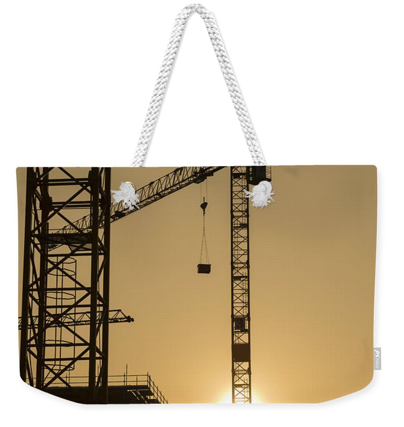 Construction Crane Weekender Tote Bag featuring the photograph Construction Cranes by Mats Silvan