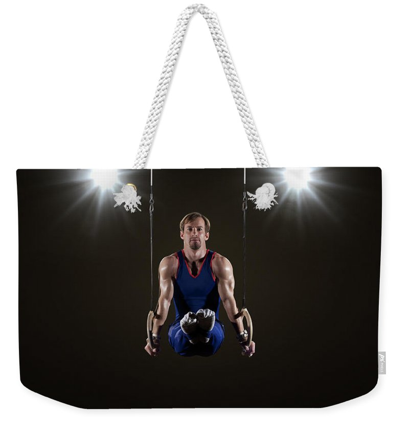 Expertise Weekender Tote Bag featuring the photograph Male Gymnast On Rings by Mike Harrington