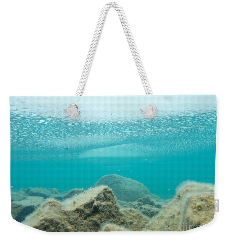 Above Weekender Tote Bag featuring the photograph Ice Floats In Shallow Lake With Rock Reflections by Stephan Pietzko