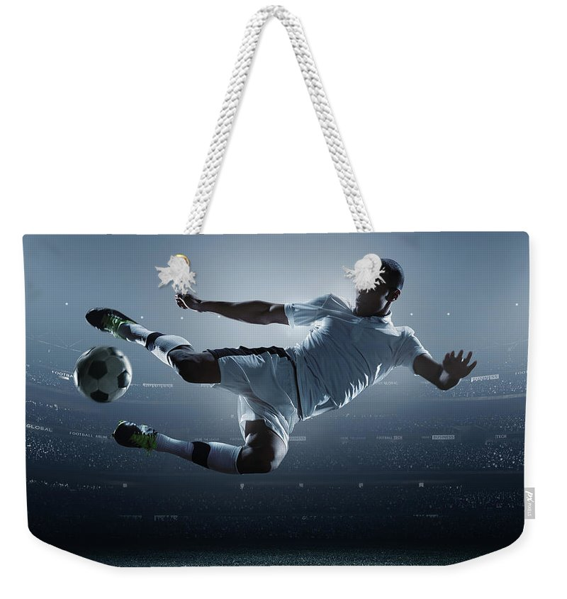 Goal Weekender Tote Bag featuring the photograph Soccer Player Kicking Ball In Stadium by Dmytro Aksonov