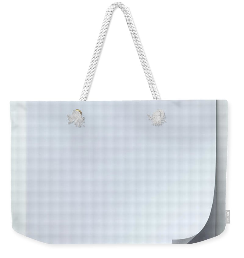 Shadow Weekender Tote Bag featuring the photograph A Blank Sketch Pad With Curled Up Page by Caspar Benson