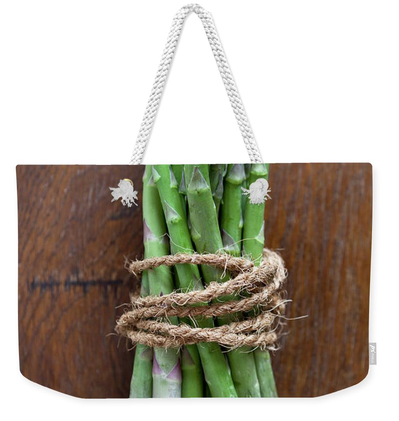 Kitchen Weekender Tote Bag featuring the photograph A Bundle Of Asparagus by Halfdark
