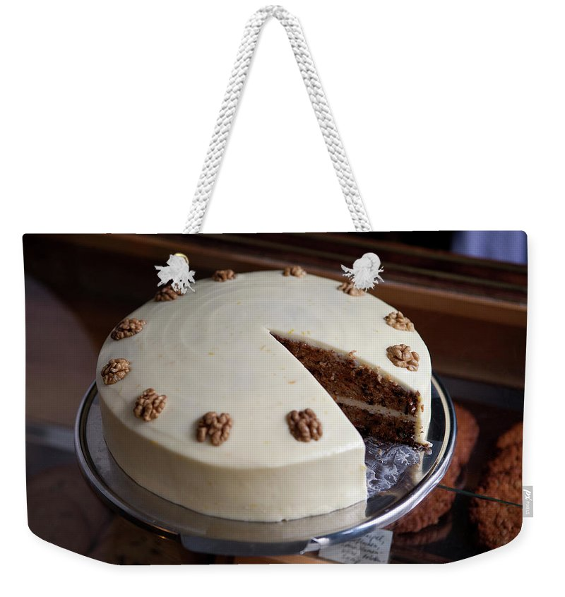 Unhealthy Eating Weekender Tote Bag featuring the photograph A Carrot Cake On A Display Cabinet In A by Halfdark