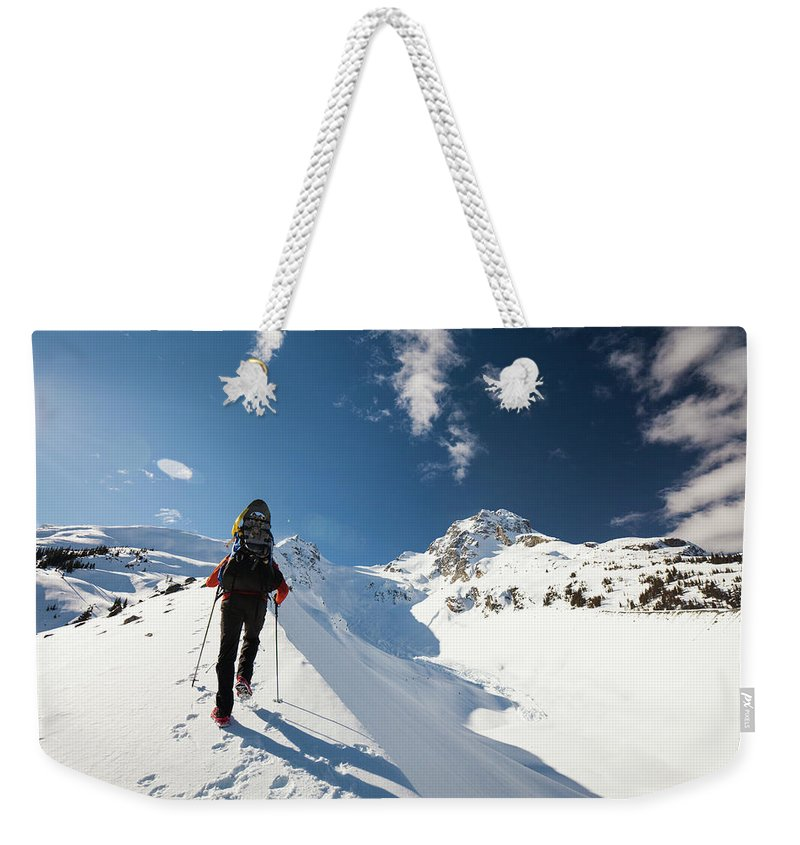 Color Image Weekender Tote Bag featuring the photograph A Climber Walks Along The Snow Covered by Christopher Kimmel