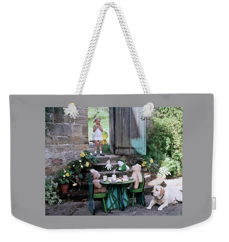 Children Weekender Tote Bag featuring the photograph A Dog Sitting Next To Two Teddy Bears Having by Ernst Beadle