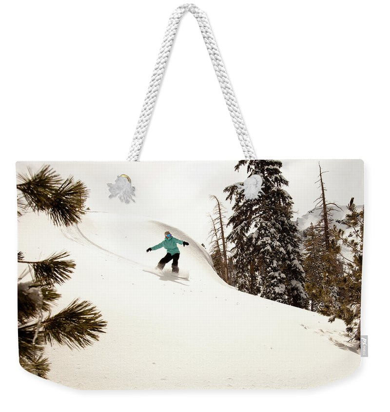 California Weekender Tote Bag featuring the photograph A Female Snowboarder Lays Out Some by Kyle Sparks