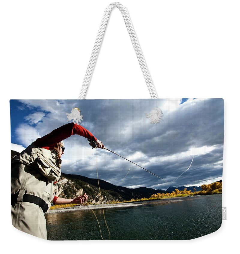 20-24 Years Weekender Tote Bag featuring the photograph A Fly Fisher Casting His Line by Patrick Orton