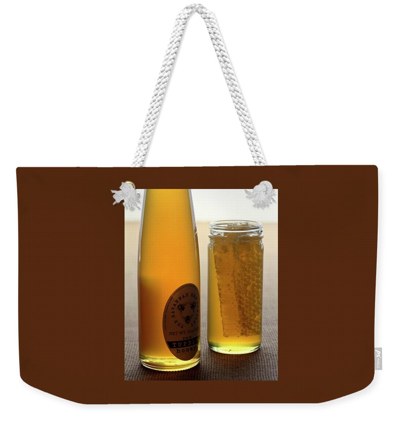 Condiment Weekender Tote Bag featuring the photograph A Jar And Bottle Of Honey by Romulo Yanes