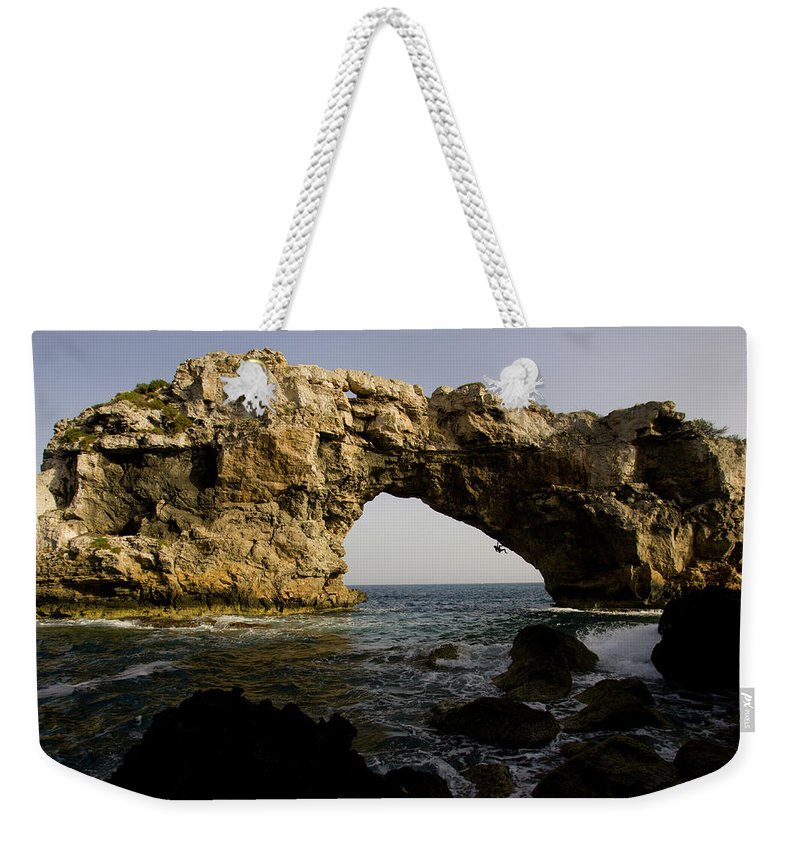 Action Weekender Tote Bag featuring the photograph A Man Rock Climbing Deep Water Soloing by Corey Rich