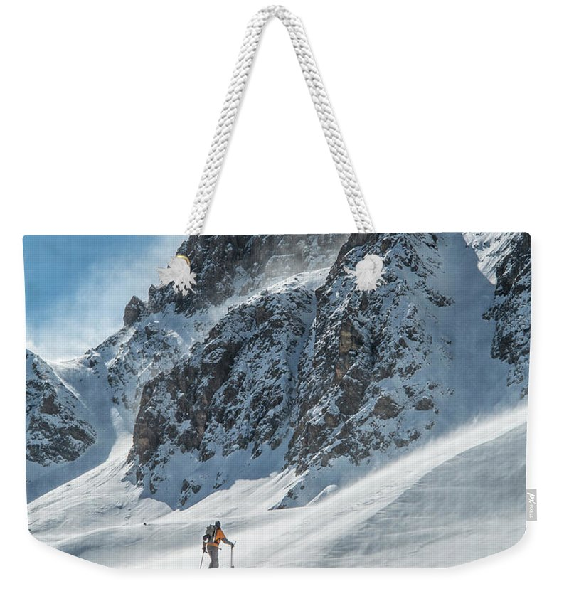 Adventure Weekender Tote Bag featuring the photograph A Man Ski Touring In The Mountains by Whit Richardson