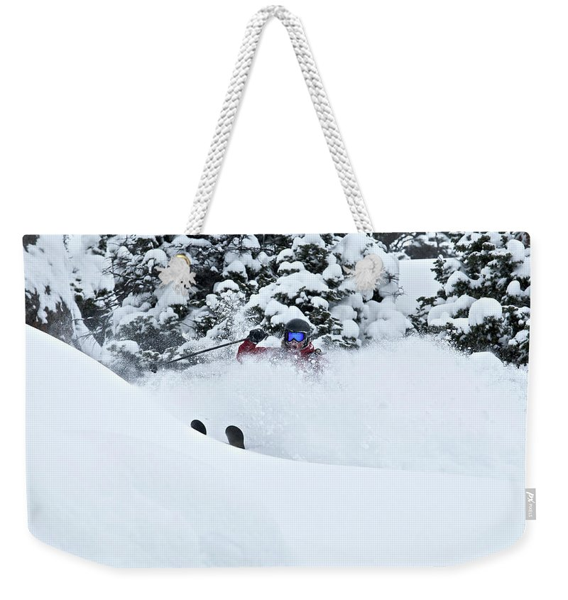 Adult Weekender Tote Bag featuring the photograph A Man Skis On Teton Pass In Wyoming by Derek DiLuzio